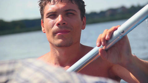 Close-up of young shirtless man paddling boat. Tourism, vacation Footage