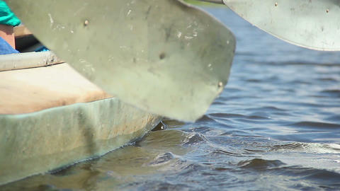 Close-up paddles entering water, rowing boat. Couple on vacation Footage