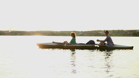 Young relaxed couple having rest on boat after rowing exercise Footage