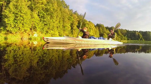Man and woman paddling canoe synchronously on beautiful river Footage