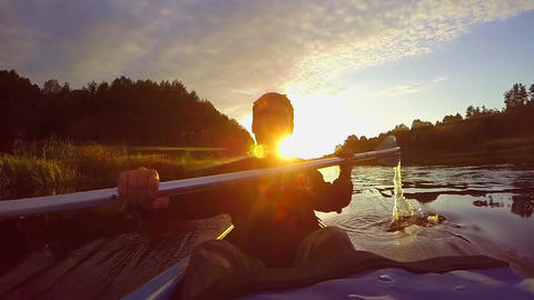 Silhouette of young happy man paddling kayak at sunset, slow-mo Footage