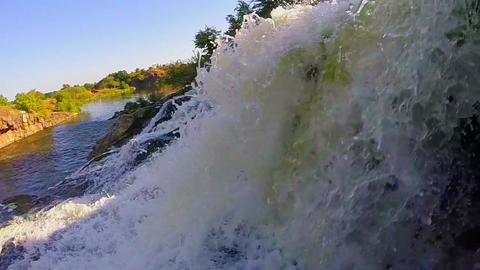 Closeup, waterfall falling into river, beautiful nature, sunset Footage