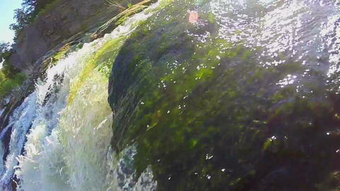 Closeup of green water running over the rocks, waterfall, slowmo Footage