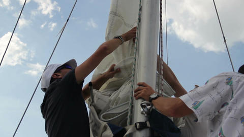 Closeup yacht crew letting down the sails. Yachting, sailing Footage