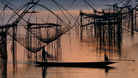 Asia Fishermen in the early morning golden light casting sow net fish at Klong P Footage