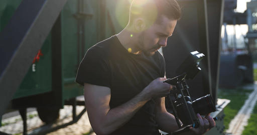 Male Filmmaker in black film handheld the sunset. Industrial sunny footage Live Action