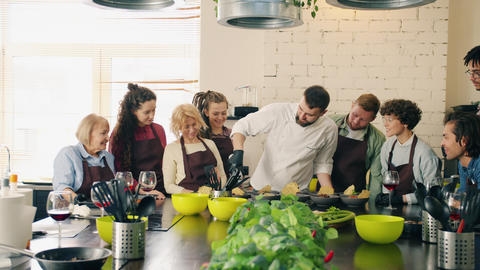 Professional chef teaching group of students making meals and talking in kitchen Live Action