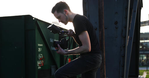 Male young caucasian Filmmaker in black with beard film handheld the sunset Live Action