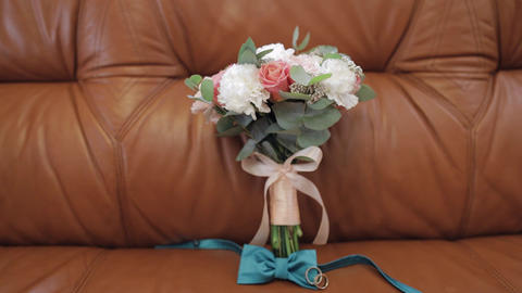 Beautiful wedding bouquets lie with wedding rings and grooms bow tie on sofa Live Action