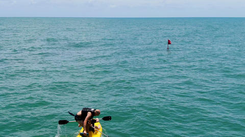 Aerial view view of strong young active men kayaking on the clear blue turquoise Live Action