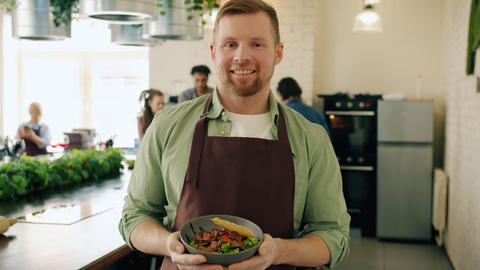 Portrait of attractive guy in apron standing in cooking class with bowl of tasty Live Action