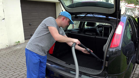 man hoovering black car boot with vacuum cleaner outdoor. 4K Live Action