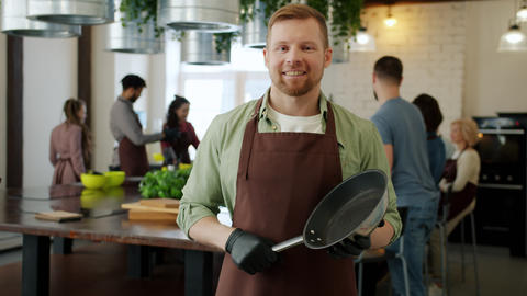 Portrait of attractive bearded guy standing in cookery school holding frying pan Live Action