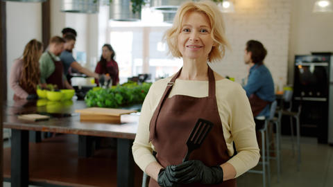 Portrait of attractive mature blonde in apron smiling indoors in cookery school Live Action