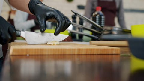 Slow motion of chef's hands chopping garlic during meal preparation in kitchen Live Action