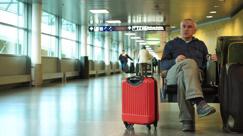 Helsinki / Finland - November 1 2019: White man with red luggage case waiting for plane in Helsinki Live Action