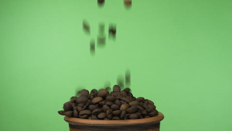 Coffee beans fall into a crowded clay bowl and fall out of it. Isolated on a Live Action