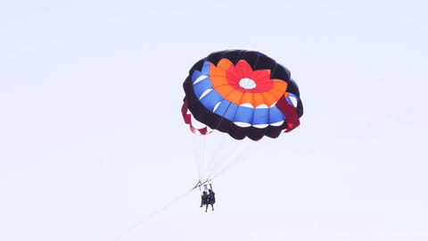 Tourists on a parachute over the sea. Parasailing in the red sea. Holidays Live Action