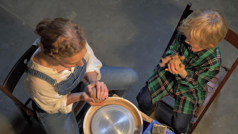 Top view, woman with boy prepare material for work on the pottery wheel Live Action