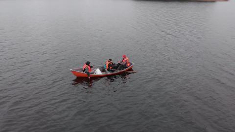 Three men wearing orange life jackets in orange boat on lake in Finland aerial spiral Live Action