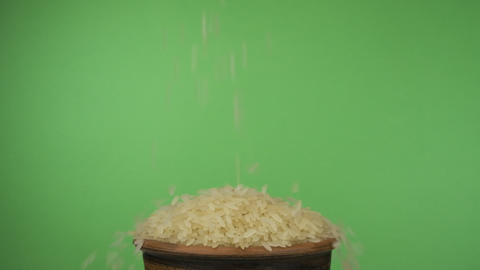Rice grains fall into a crowded clay bowl and fall out of it. Isolated on a Live Action