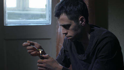 Man heating heroin dose in spoon with lighter Live Action