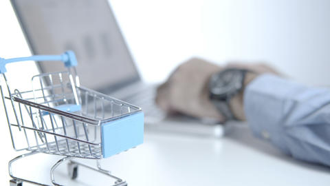 Man use laptop choosing items and buying online in online store with cart on white desk, shopping Live Action