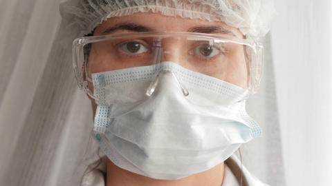 doctor in protective mask and protective goggles looking at camera, portrait Live Action
