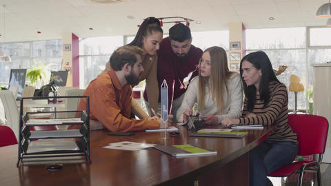 Group of adult Caucasian students discussing university project indoors Live Action