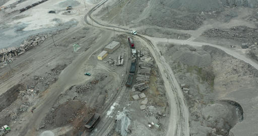 Heavy equipment digs and hauls ore inside an enormus open pit mine Live Action