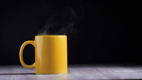 Hot water in yellow mug with steam smoke Live Action