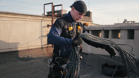 Industrial climber in uniform stands on the roof of high-rise building and picks Live Action