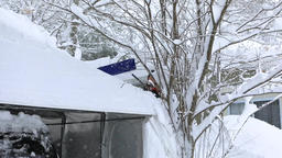 Man removes snow from canopy over car in a winter scene Live Action