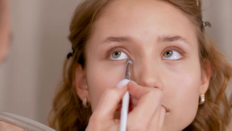 Applying makeup. Giving the eyes of the young girl's expression. Stroke the eye Live Action