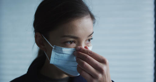 Woman putting on surgical face mask for protection against coronavirus. SLOW Live Action