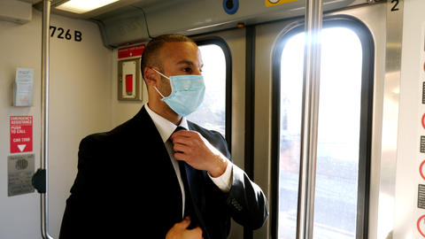 Businessman wearing face mask rides train to work Live Action