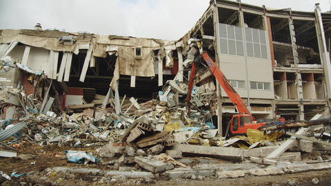 red excavator disassembles debris rubble of hockey stadium Live Action