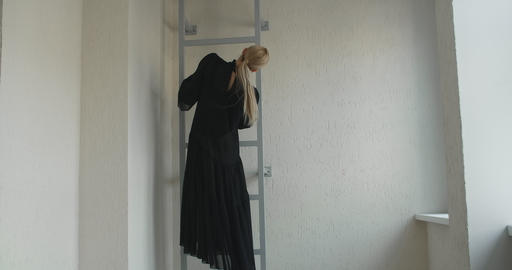 Blonde attractive female dancer with make up in long black dress does ballet Live Action