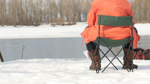 A fisherman sits on a stool and catches fish in the winter. River flow. Slow Live Action