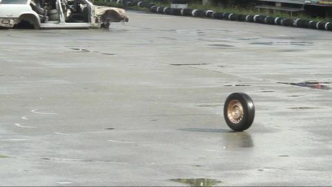 Car wheel rolling on asphalt after accident, crash. Junkyard Footage