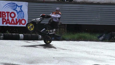Stunt person rides scooter on one wheel and suddenly falls Footage
