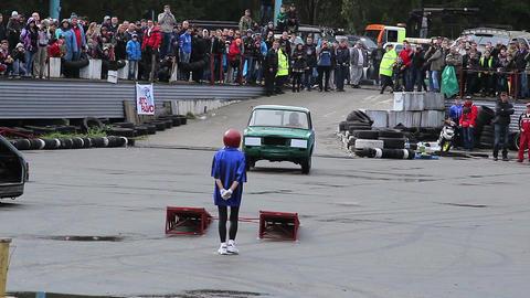 Petite stunt woman dives under fast-driving car, auto show Live Action