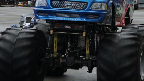 Monster truck huge wheels crashing junk cars, entertaining crowd Live Action
