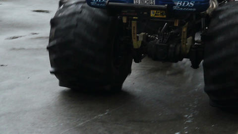 Huge monster truck circling at arena, crushing junk cars, show Live Action