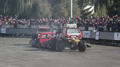Two monster trucks pushing squeezing junk cars at sporting event Live Action