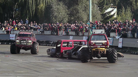 Audience watching two monster trucks at arena, extreme sports Live Action