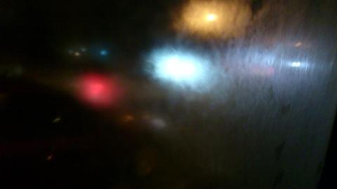 Looking through wet window on dark road, intensive night traffic Footage
