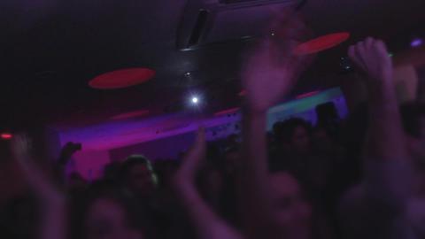 Crowd at nightclub, dancing, enjoying music, waving hands Live Action