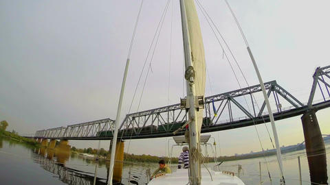 Tourist yacht sailing under river railway bridge, moving train Footage