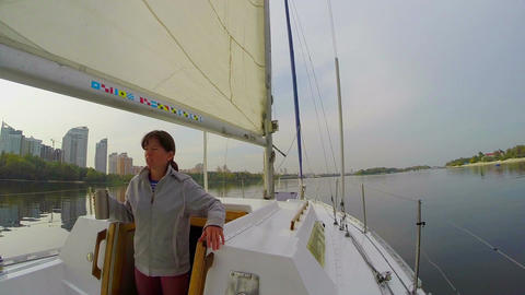 Sailboat on wide city river, girl leaves cabin, yachting tourism Footage